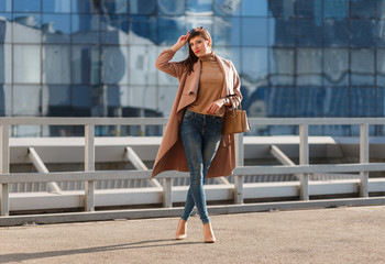 Portrait of beautiful brunette young woman in nice brown beige coat, denim jeans and sunglasses. Genuine leather bag, high heels shoes. Spring autumn fashion trendy photo of lady on urban background.