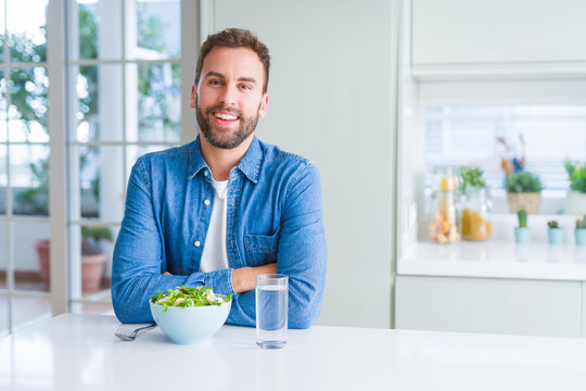 Handsome man eating fresh healthy salad happy face smiling with crossed arms looking at the camera. Positive person.