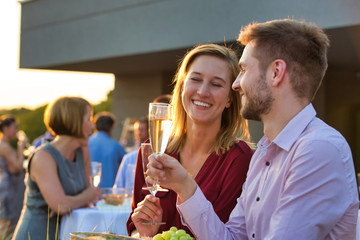 Smiling business colleagues standing at table during rooftop party Wall mural