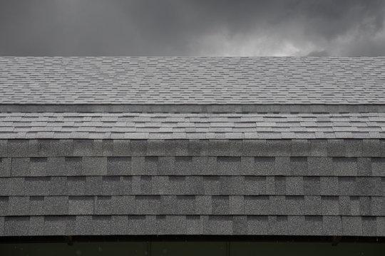 wet black shingle roof while raining dark. asphalt tiles on the roof on cloudy day.