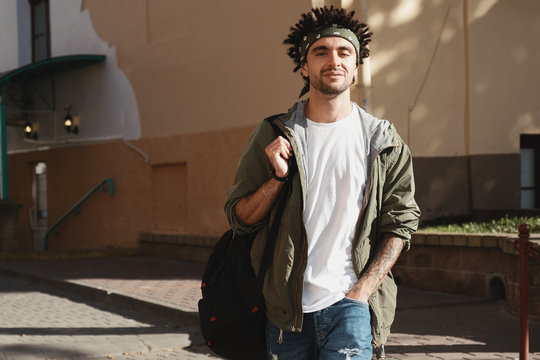 Handsome bearded young man with dreadlocks hairstyle dressed fashionable clothes walking in city street. Autumn fashion outfit, outdoor portrait, urban style, casual look
