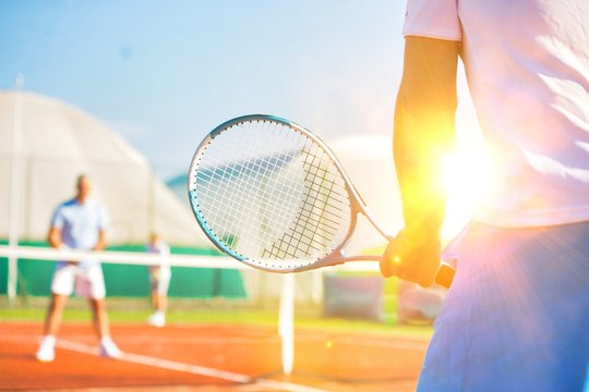 Active seniors playing tennis on sunny day at red court with yellow lens flare in background