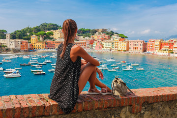 Fotobehang Liguria Tourist woman in Sestri Levante, Liguria, Italy. Scenic fishing village with traditional houses and clear blue water. Summer vacation rich resort with picturesque harbour and nice sand beach