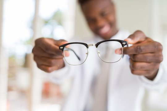 African american optiian man holding and showing glasses lens to custumers at the optics shop while smiling confident