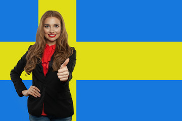 Sweden. Happy cute student girl with thumb up against the Sweden