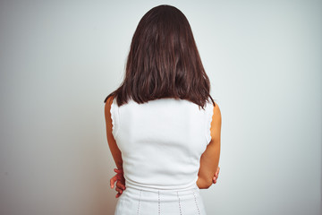 Young beautiful woman wearing dress standing over white isolated background standing backwards looking away with crossed arms