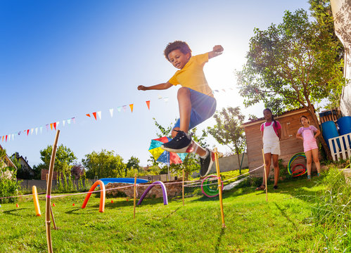 Boy jump over strings passing course of obstacles
