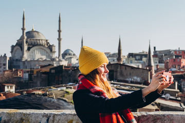 Blond woman makes photo on the phone on the roof of the Grand Bazaar, Istanbul, Turkey. Girl in a yellow hat takes a selfie on a sunny autumn day. Traveler girl walks through winter Istanbul.
