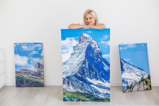 Happy blonde woman hanging large picture on wall at home