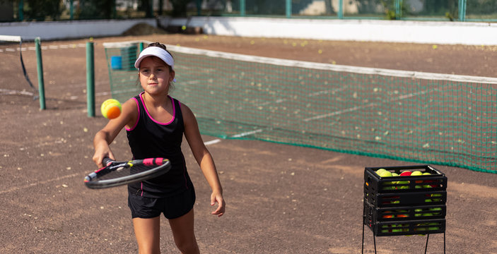 Portrait of tennis player girl training on court.