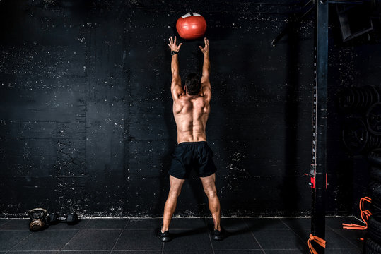 Young strong sweaty focused fit muscular man with big muscles doing throwing medicine ball up on the wall for training hard core workout in the gym real people selective focus
