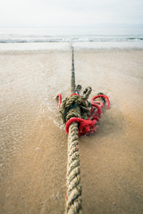 Red knotted ships rope 7. Creative red knotted ships rope lying on a sandy beach leading out to sea on the shoreline as the tide comes in.