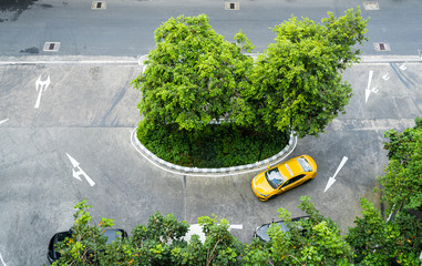 Yellow Thai taxi cab driving in Bangkok city center standing out from the grey asphalt from above.