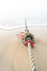 Red knotted ships rope 6, Creative red knotted ships rope lying on a sandy beach leading out to sea on the shoreline as the tide comes in.