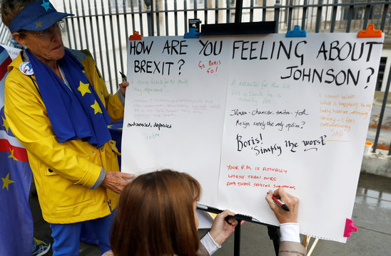 A woman writes a message on a board set up by Anti-Brexit protesters opposite the Houses of Parliament in Westminster in London