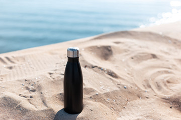 Matte black steel thermo bottle for water in sand of the beach on background of sea. Empty blank for mockup.