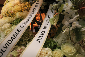 A picture of Spanish singer Camilo Sesto is seen through a wreath of flowers during his wake in Madrid