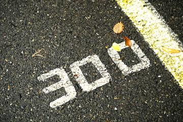 Number three hundred on a wet asphalt road.