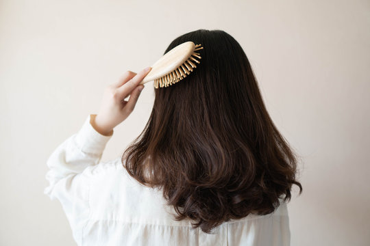 Back view of young beautiful woman in white shirt with long black curly hair combing her hair in the morning. Hair care concept.