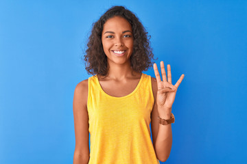 Young brazilian woman wearing yellow t-shirt standing over isolated blue background showing and pointing up with fingers number four while smiling confident and happy.