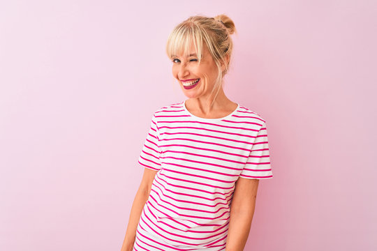 Middle age woman wearing striped t-shirt standing over isolated pink background winking looking at the camera with sexy expression, cheerful and happy face.