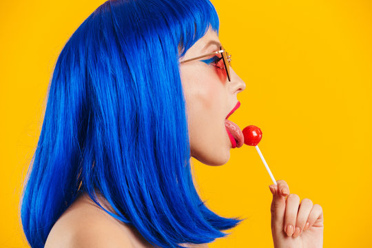 Portrait in profile of glamorous nice young woman wearing blue wig and sunglasses licking lollipop
