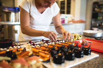 Young woman decorating raspberry cookies,stock photo