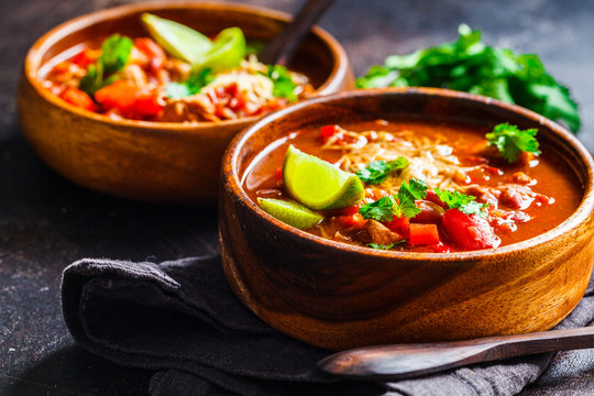 Traditional mexican bean soup with meat and cheese in wooden bowl, dark background. Mexican food concept.
