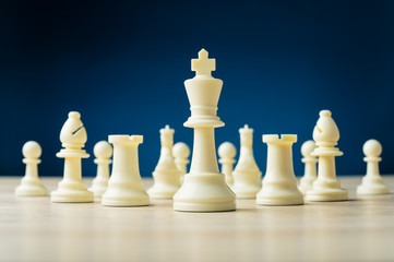 White chess pieces with king in front placed on wooden desk
