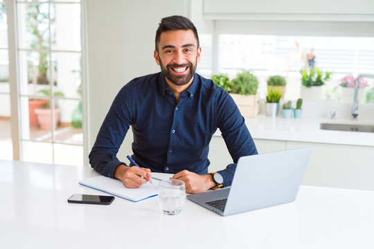 Handsome hispanic man working using computer and writing on a paper with a happy face standing and smiling with a confident smile showing teeth
