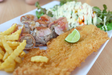 Fried fish and bacon served with french fries and salad