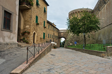 Architectural details of old houses at narrow street of Volterra with Medici fortress in background, Tuscany, Italy