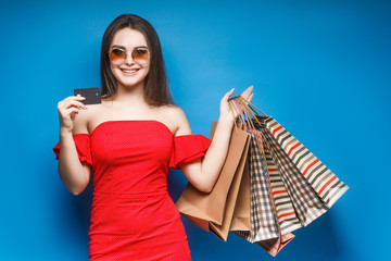 Picture of a cheerful young brunette woman in summer dress holding credit card posing with shopping bags and looking at camera over blue background.
