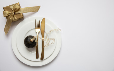 Table setting, xmas, new year. Gold cutlery on white set of dishes, white background