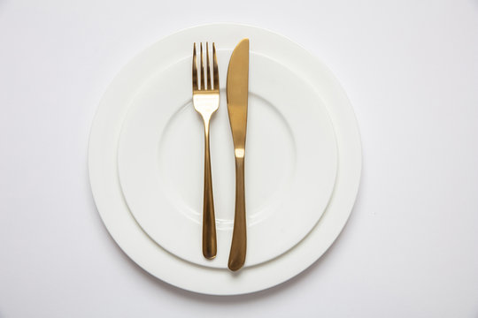 Table setting, formal. Gold cutlery on white set of dishes, white background