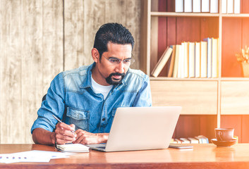 30s handsome businessman take a short note on paper while reading article from internet.  Modern arab businessman in casual clothes working at home.