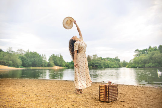 Girl having fun, running on the beach at the lake