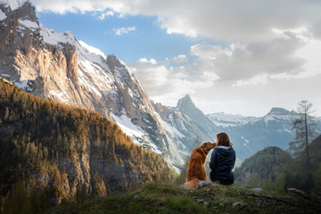 girl with a dog in the mountains. Autumn mood. Traveling with a pet. Nova Scotia Duck Tolling Retriever