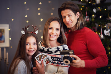 Beautiful family celebrating Christmas at home and taking instant pictures