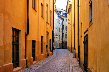 Fototapete - Bright yellow buildings on a narrow cobblestone street in Gamla Stan, the Old Town of Stockholm, Sweden