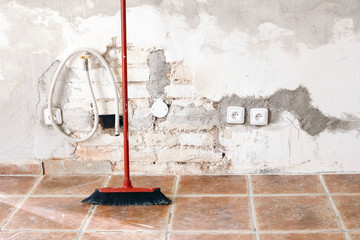 Unfinished room reconstruction. Home repair, improvement. Work in progress. Red broom against white brick wall. Cleaning and rebuilding, renovation concept. Old apartment under construction.
