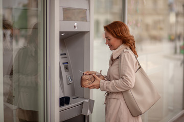 One mature woman, using ATM machine, putting credit card in her wallet.