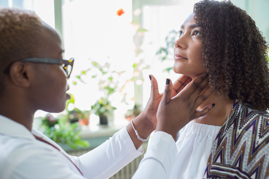 An African American female doctor examines with her fingers, palpates her neck and lymph nodes. Pain in the neck. Mixed race doctor and patient