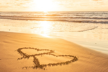 Valentines day on sunny beach. Two hearts drawn in sand, love concept