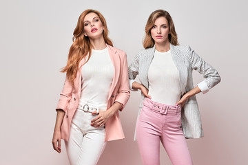 Wall Mural - Fashionable autumn woman well dressed with stylish hairstyle, makeup. Two Gorgeous Girl in Trendy fall outfit, fashion hair. Graceful blonde redhead glamour female model, make up, autumnal portrait