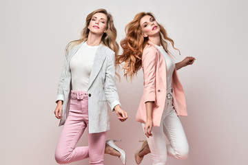 Fashionable autumn woman dance having fun with stylish hairstyle, fall makeup. Two Excited funny Girl, Trendy coral pink outfit, fashion wavy hair. Gorgeous female model, autumnal dancing concept Wall mural