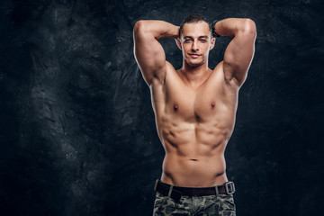 Handsome muscular man without t shirt is posing for photographer at dark photo studio.