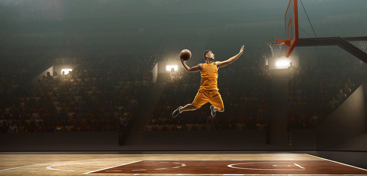 Professional basketball player on sports arena in action with the ball. Slam dunk