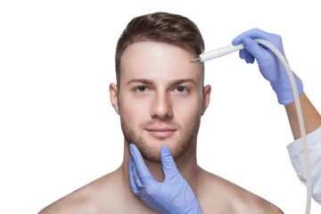 Men's cosmetology. Beautician makes a man a procedure to remove acne from his face.