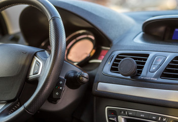 Luxurious car interior. Dashboard and steering wheel in black gray color. Transportation, design, modern technology concept.